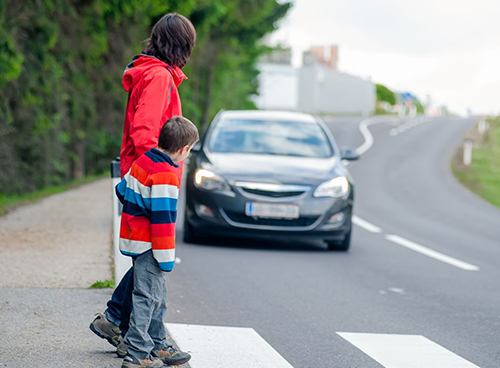 18256202 - mother and son passing a street when a car coming